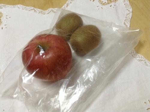 キウイ2個とリンゴ1個をナイロン袋に入れている