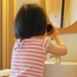 子供が洗面所でうがいをする様子