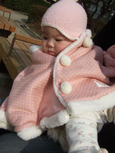 赤ちゃんの城のケープと帽子をかぶる娘
