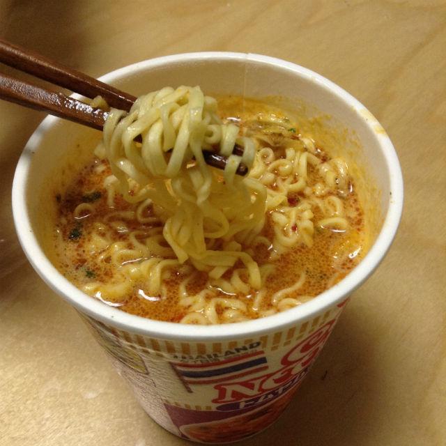 日清カップヌードル「トムヤムクンヌードル」(日本版)をかき混ぜて食べる様子
