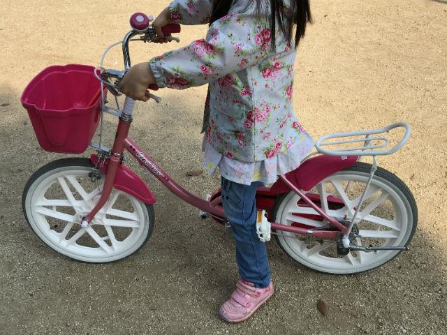 補助輪無し自転車のサドルにまたがった様子