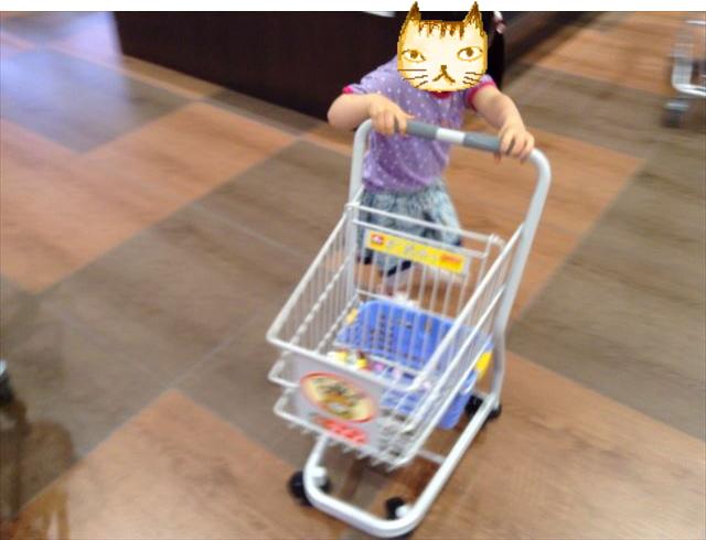 スーパーのお手伝いカートを押している娘