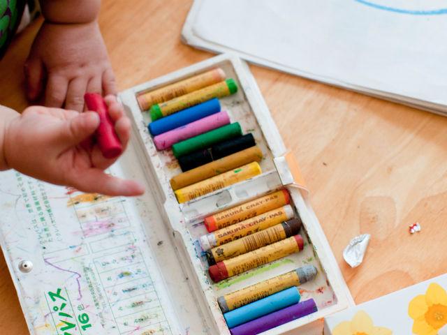 幼稚園でクレヨンを使ってお絵かきしている