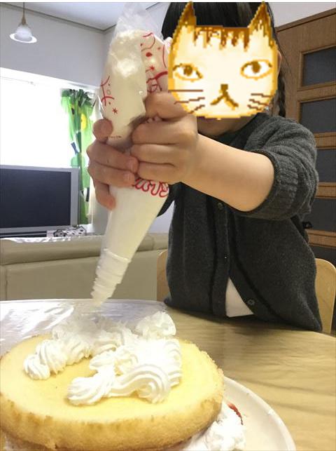 ケーキ生地「つくってHAPPY」と「らくらくホイップ」をのせている娘