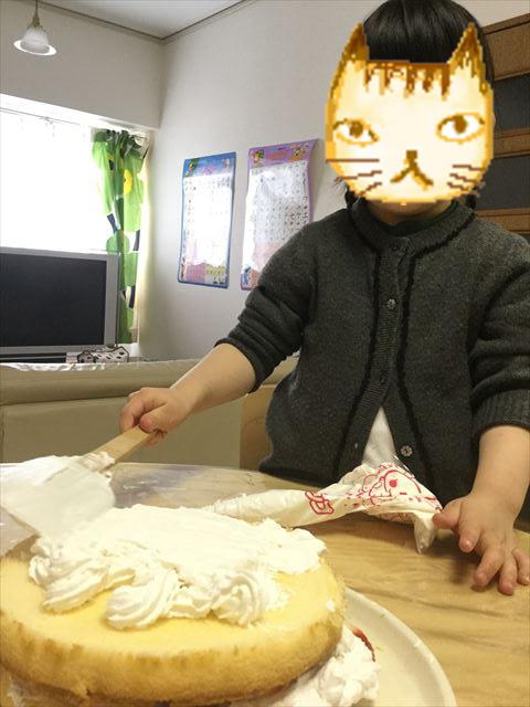 ケーキ生地「つくってHAPPY」と「らくらくホイップ」を平らに塗っている娘の様子