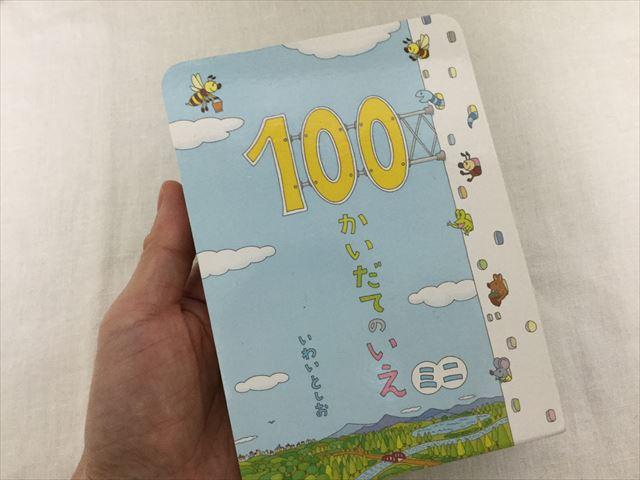 絵本「100かいだてのいえ・ミニ」(偕成社)を手に持ったところ