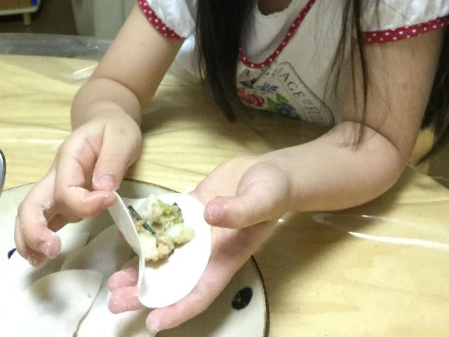 子供が餃子の皮に餡を包んでいる