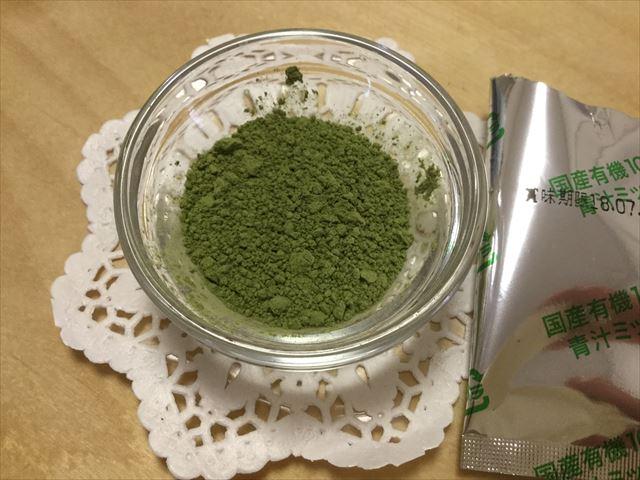 有機栽培「青汁ミックス」の粉末を容器に移した様子
