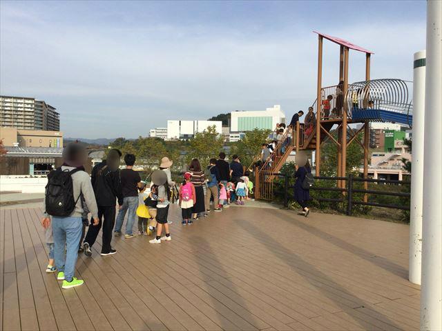 彩都西公園のローラー滑り台に並ぶ子供とその保護者