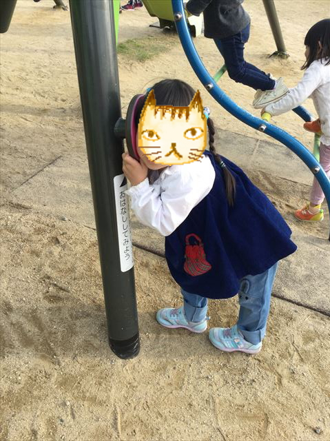 彩都西公園のバッタ滑り台、音声を聞いている子供