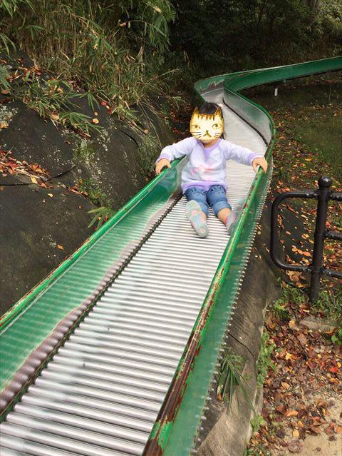 千里東町公園のロングスライダーを滑る子供