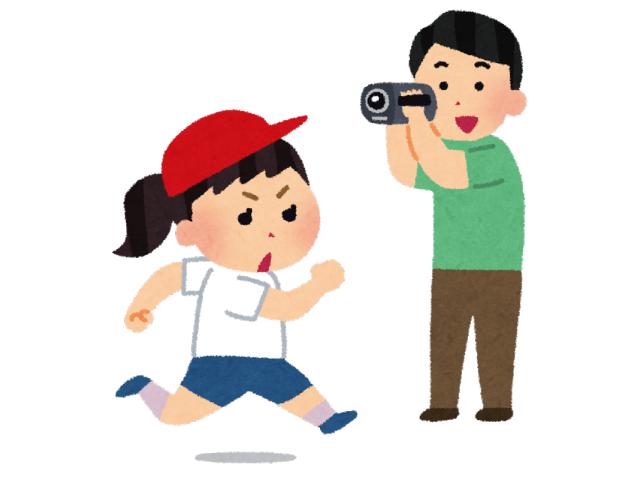 運動会でかけっこする子供を撮影する親