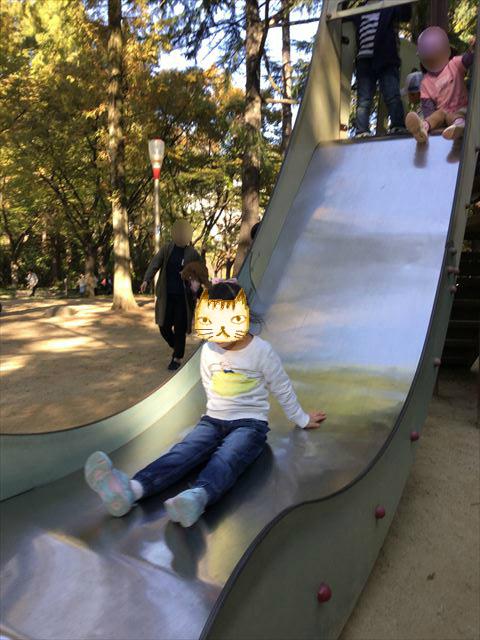 靫公園の遊具、滑り台を滑る娘