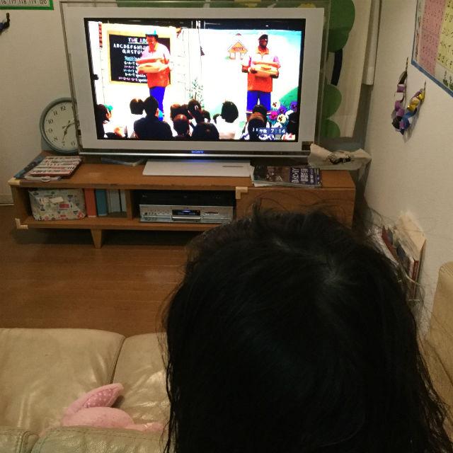ワールドファミリーの週末イベントの映像を見ている子供