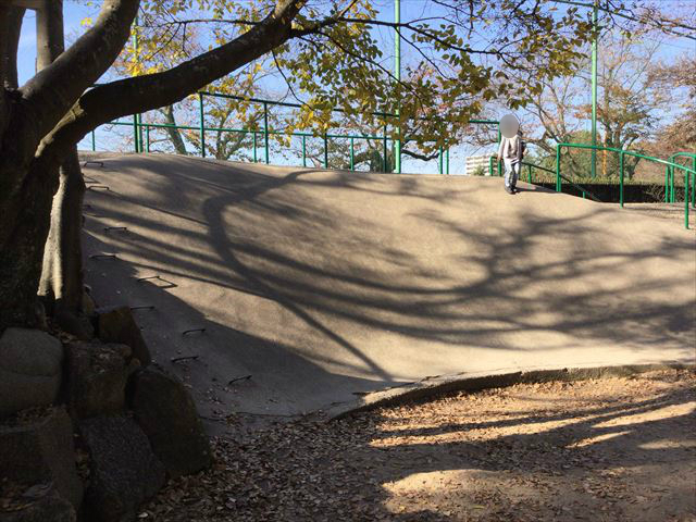 「明石公園」こども広場の遊具、石の滑り台