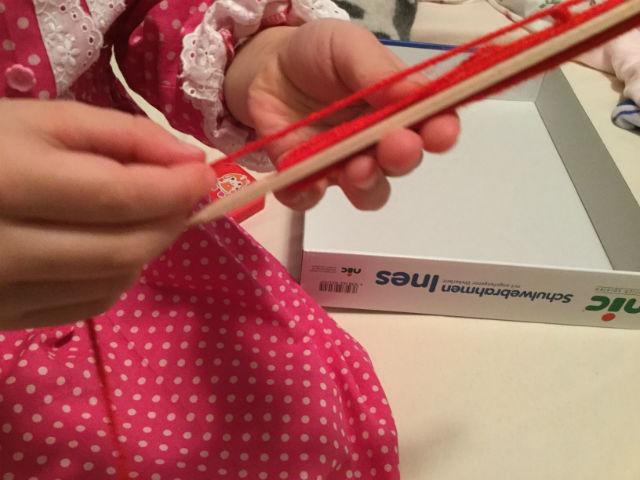 ニック社の機織り機「イネス(Ines)」子供が毛糸を巻いている様子