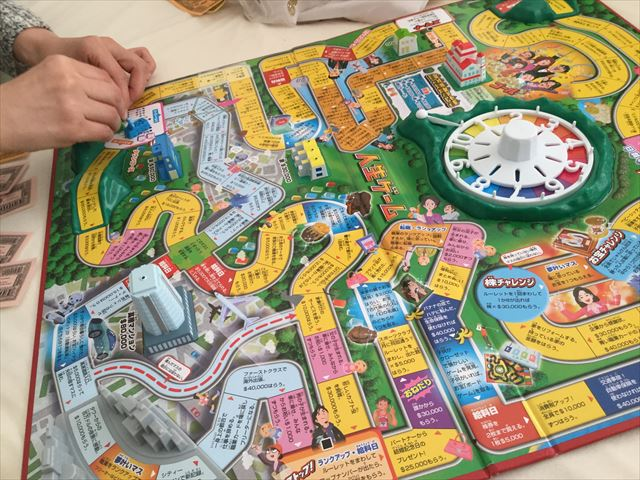人生ゲームを家族で遊んでいる様子
