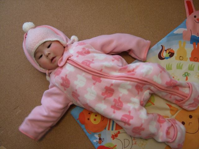 赤ちゃんにスリーパーを着せている