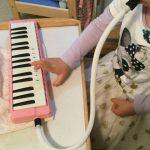 鍵盤ハーモニカを拭いている子供