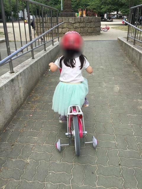 ブリジストンのエコキッズカラフル(18インチ)ピンクに乗って公園を走っている子供の様子、後方から撮影