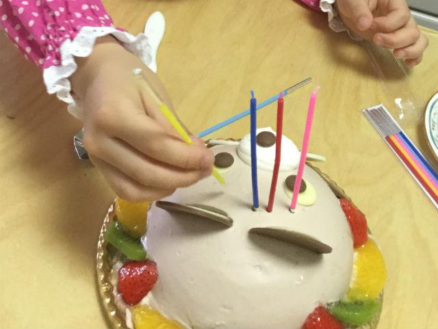 アンテノールのアニバーサリーケーキ「アニマルデコクマさんケーキ」にローソクをさしていく娘