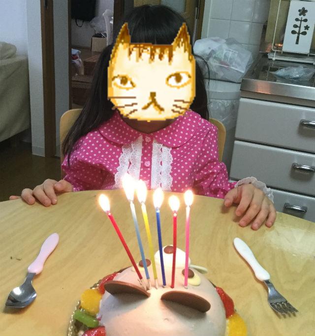 アンテノールのアニバーサリーケーキ「アニマルデコクマさんケーキ」にロウソクをさし誕生日を祝っている様子