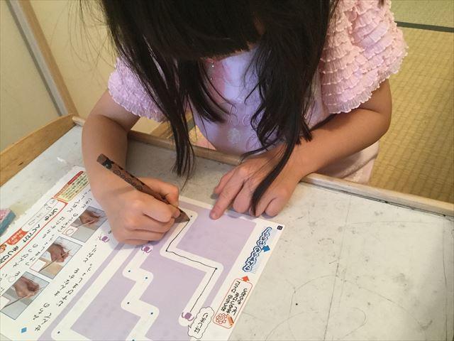 チャレンジ1年生「入学の準備国語・算数ワーク・基礎編」を学習する娘、線を丁寧にひく