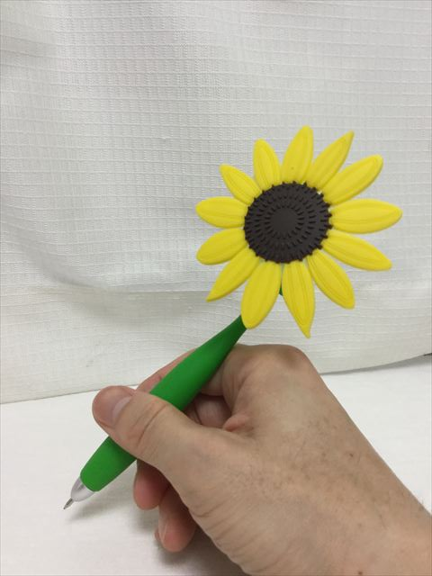 雑貨店「ASOKO」の文房具、ひまわりボールペンを持って字を書く