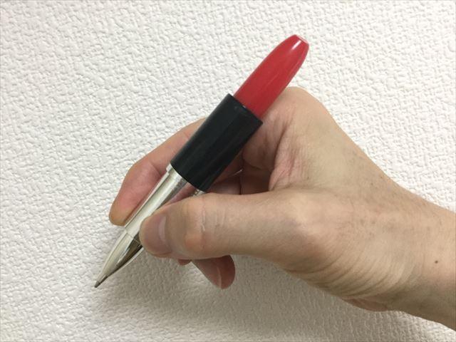 雑貨店「ASOKO」の文房具、口紅ボールペンを手に持って字を書いている
