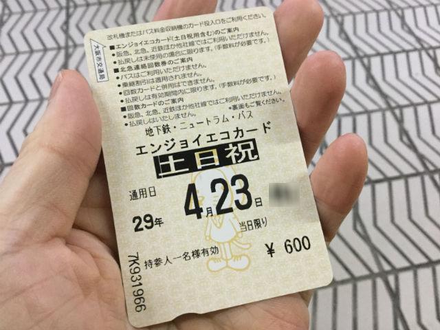 大阪市営地下鉄の1日乗車券「エンジョイエコカード」を手に持っている様子