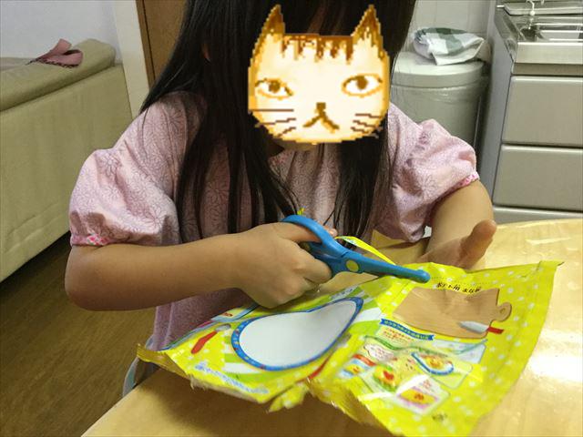 知育菓子ホッピンクッキン「つくろう!おこさまランチ」袋をはさみで切る娘の様子
