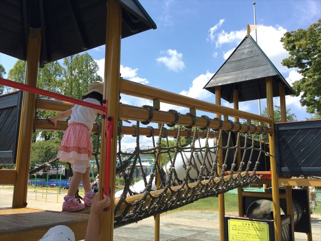 京都競馬場の公園「緑の広場」のアスレチック遊具、縄の橋を渡る娘