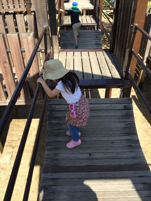 元浜緑地の木製アスレチック遊具、揺れる梯子を渡る