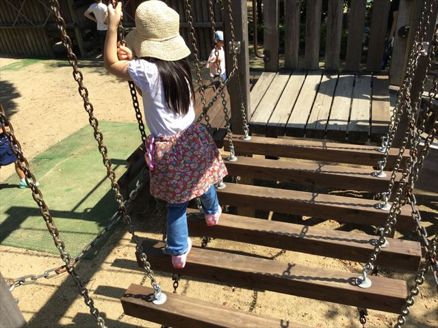 元浜緑地の木製アスレチック遊具、木と木の間に隙間がある梯子を渡る