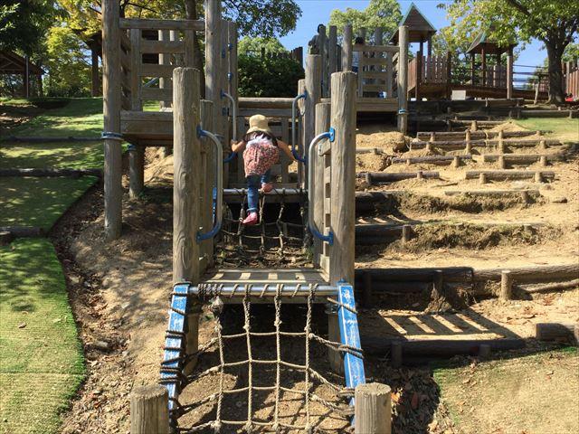 元浜緑地の木製アスレチック遊具で遊ぶ娘。縄の梯子を登る様子
