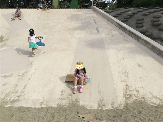 住之江公園の石の滑り台。段ボールに乗って滑る娘