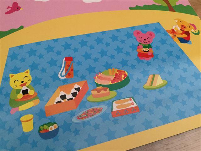 ダイソー「知育シールブック」おいしいもの、敷物にお弁当やサンドイッチのシールを貼った様子