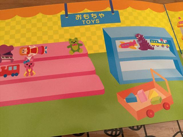 ダイソー「知育シールブック」おかいもの、おもちゃ売り場に人形やピアノなどのシールを貼った様子