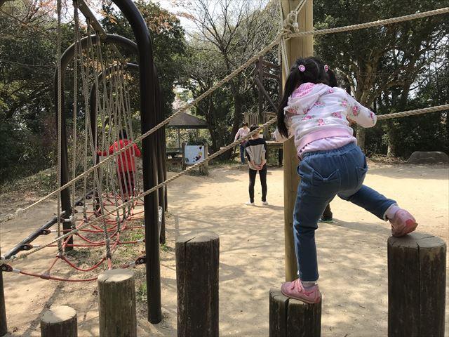 須磨離宮公園のアスレチック、綱を持ちながら丸太を飛び越える