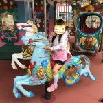 神戸王子動物園遊園地「メリーゴーランド」の馬に乗る娘