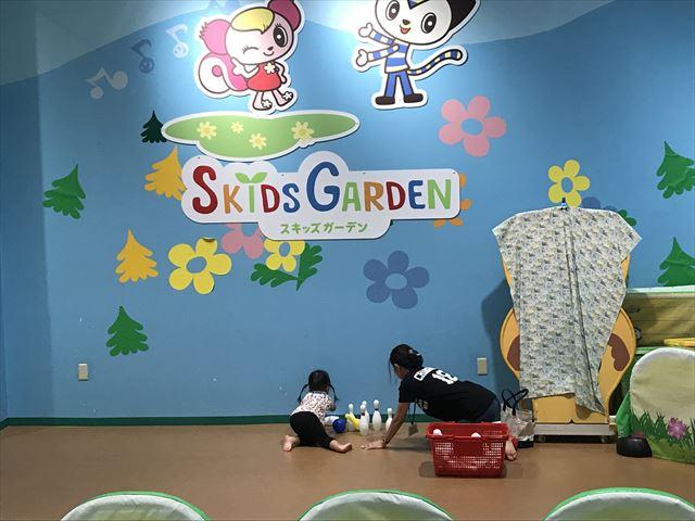 モーリーファンタジー内スキッズガーデンの看板とプレイリーダーと遊ぶ子供
