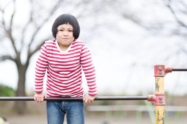鉄棒で遊んでいる元気な女の子