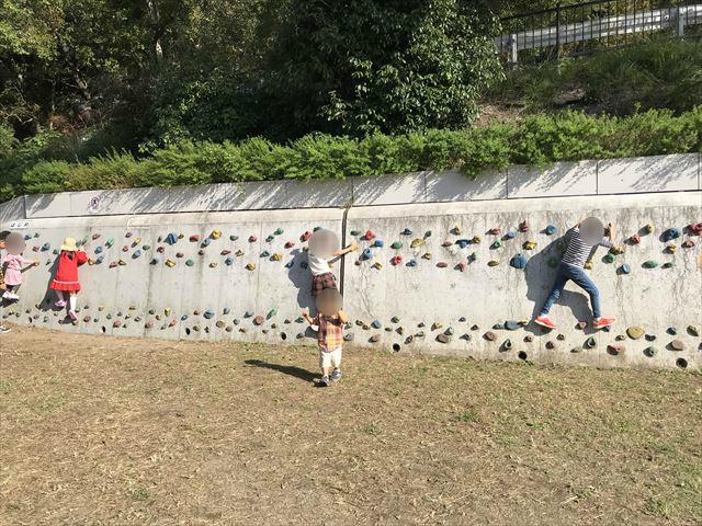 枚岡公園「みんなの広場」にあるクライミングウォールで遊ぶ複数の子供たち
