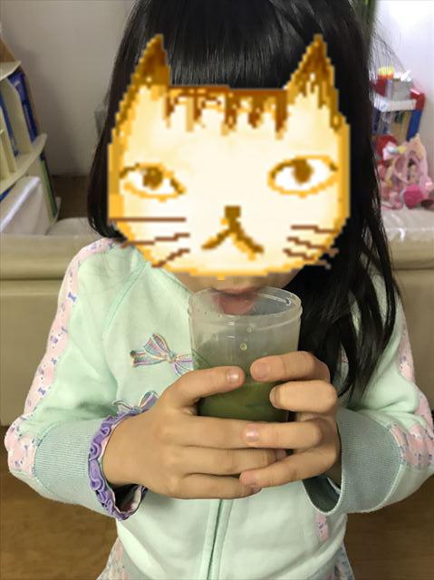 子供が「グリーンミルク」を飲んでいる様子
