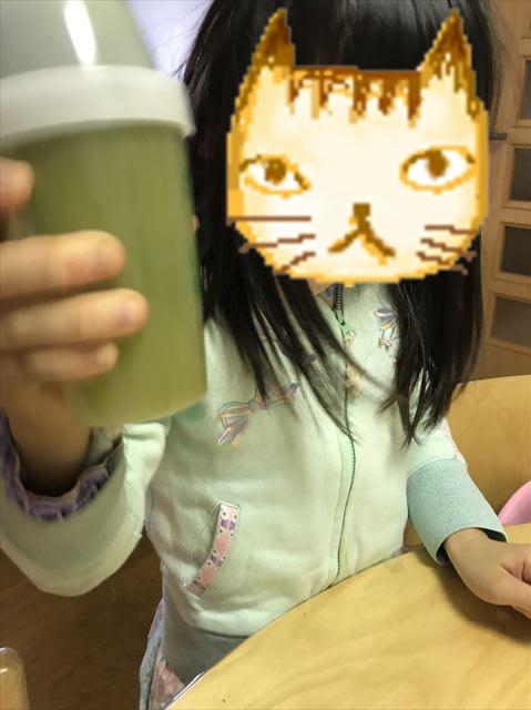 子供が「グリーンミルク」をシェイクしている様子