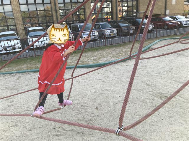 「西代蓮池公園」三角形をした縄のジャングルジムを上る娘