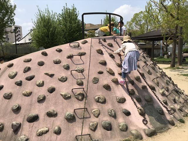 城北公園の遊具、石の滑り台を上る様子