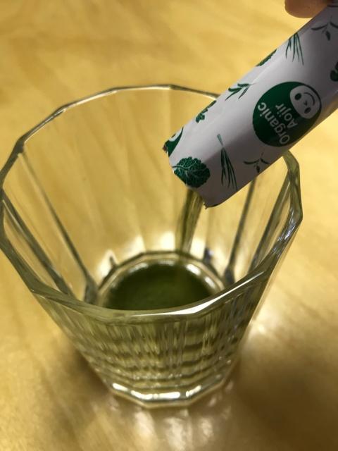 「7種の有機栽培・オーガニック青汁」1袋をグラスに入れている様子