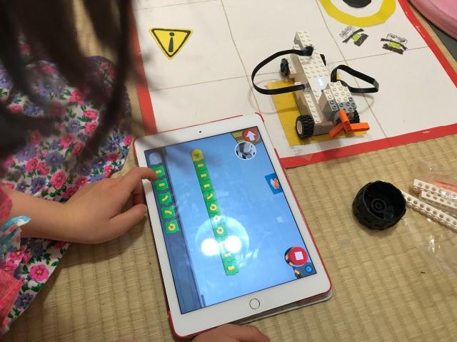 子供が「レゴブースト」のファーストステップの車をプログラミングで動かしている様子