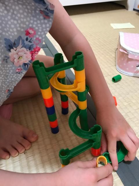 100均のビー玉転がしを組み立てている子供。自由に組み立てている